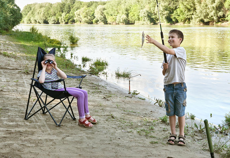 Child camping and fishing, people active in nature, boy caught fish on bait, river and forest, summer season royalty free stock images
