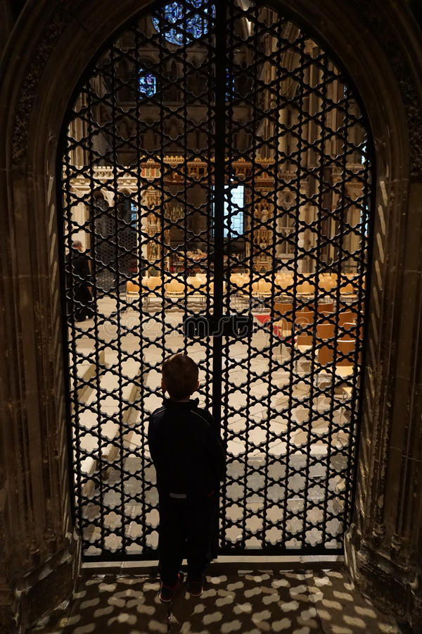 Child in Canterbury Cathedral Looking through Ornate Iron Door (interior) stock image