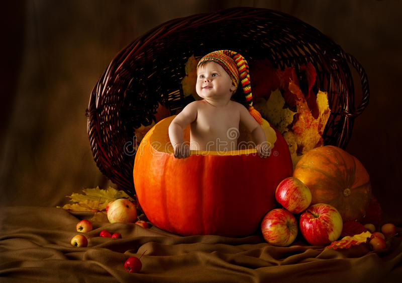 Child in cap inside pumpkin. Autumn harvest royalty free stock photo