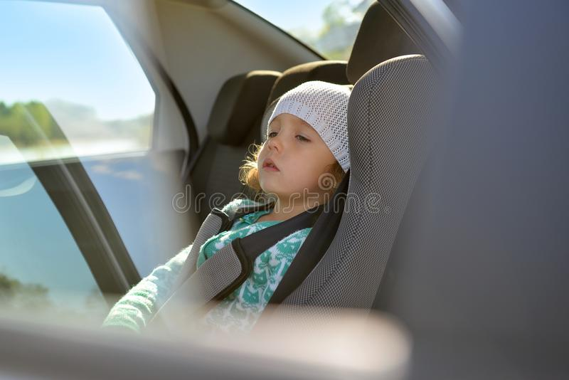 The child is in the car. Baby seat in the car. stock image