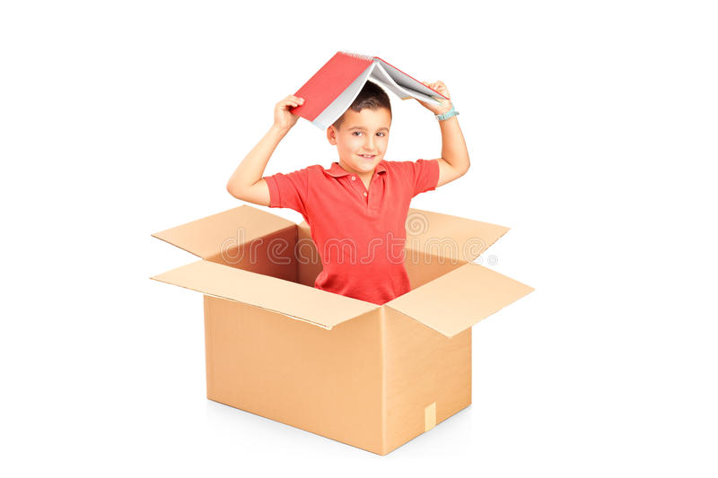 A Child In A Cardbox Holding A Book Over His Head Royalty Free Stock Photography