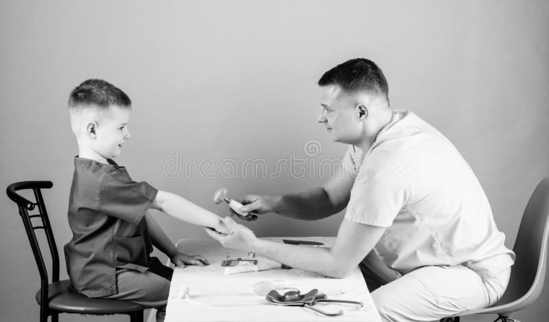 Child care. Careful pediatrician check health of kid. Medical examination. Medical service. Man doctor sit table medical. Tools examining little boy patient stock photo