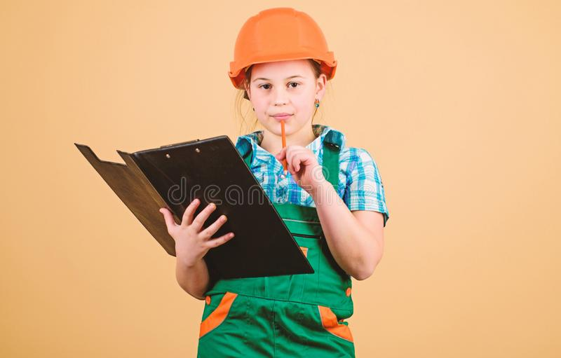 Child care development. Foreman inspector. Repair. Safety expert. Future profession. small girl repairing in workshop. Builder engineer architect. Kid worker royalty free stock photo