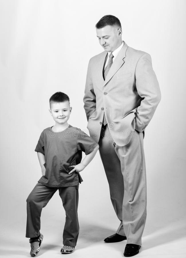 Child care development upbringing. Respectable profession. Man respectable businessman and little kid doctor uniform. Family business. Doctor respectable royalty free stock image