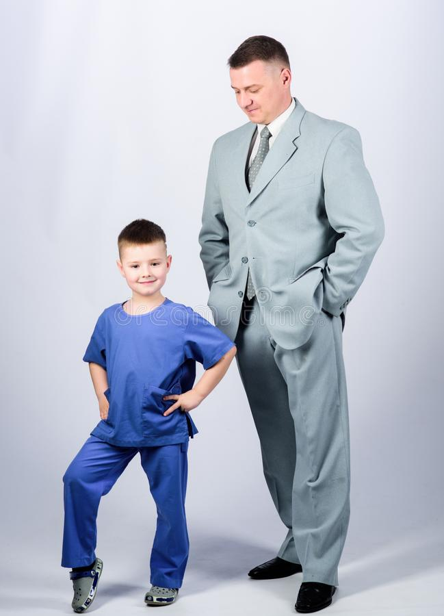 Child care development upbringing. Respectable profession. Man respectable businessman and little kid doctor uniform. Family business. Doctor respectable stock photos