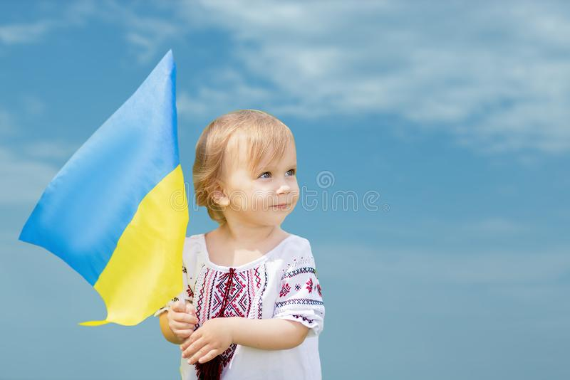Child carries fluttering blue and yellow flag of Ukraine in field. Ukraine`s Independence Day. Flag Day. Constitution day. Girl i. N traditional embroidery with stock photo
