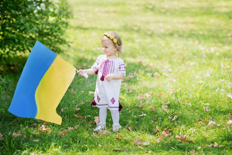 Child carries fluttering blue and yellow flag of Ukraine in field. Ukraine`s Independence Day. Flag Day. Constitution day. Girl i. N traditional embroidery with stock photography