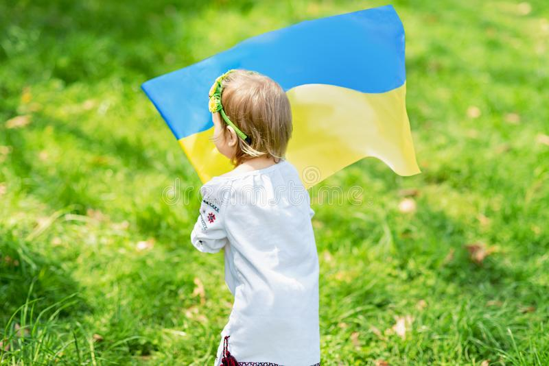 Child carries fluttering blue and yellow flag of Ukraine in field. Ukraine`s Independence Day. Flag Day. Constitution day. Girl i. N traditional embroidery with stock images
