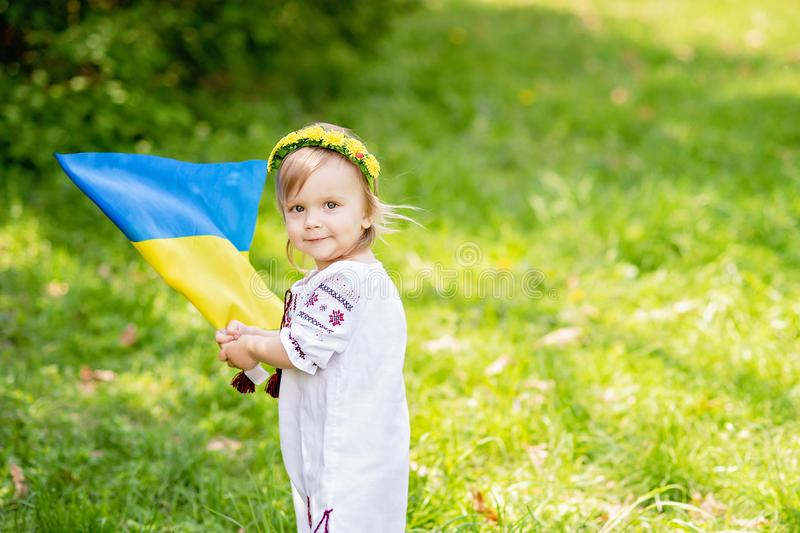 Child carries fluttering blue and yellow flag of Ukraine in field. Ukraine`s Independence Day. Flag Day. Constitution day. Girl i. N traditional embroidery with royalty free stock photo