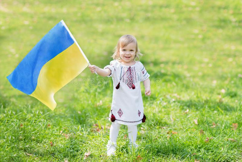 Child carries fluttering blue and yellow flag of Ukraine in field. Ukraine`s Independence Day. Flag Day. Constitution day. Girl i. N traditional embroidery with stock image