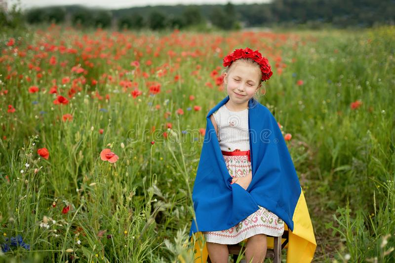Child carries fluttering blue and yellow flag of Ukraine in field. Ukraine`s Independence Day. Flag Day. Constitution day. Girl i. N traditional embroidery with royalty free stock images