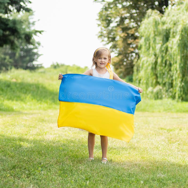 Child carries fluttering blue and yellow flag of Ukraine in field. Ukraine`s Independence Day. Flag Day. Constitution day. Girl i royalty free stock photos