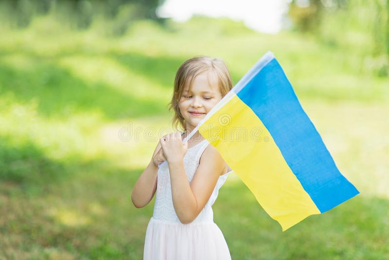 Child carries fluttering blue and yellow flag of Ukraine in field. Ukraine`s Independence Day. Flag Day. Constitution day. Girl i royalty free stock photography