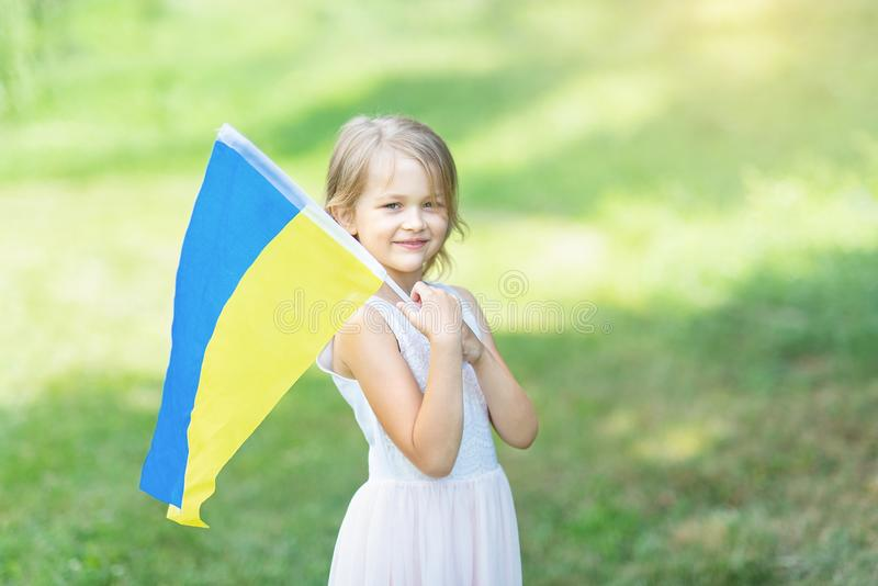 Child carries fluttering blue and yellow flag of Ukraine in field. Ukraine`s Independence Day. Flag Day. Constitution day. Girl i stock image