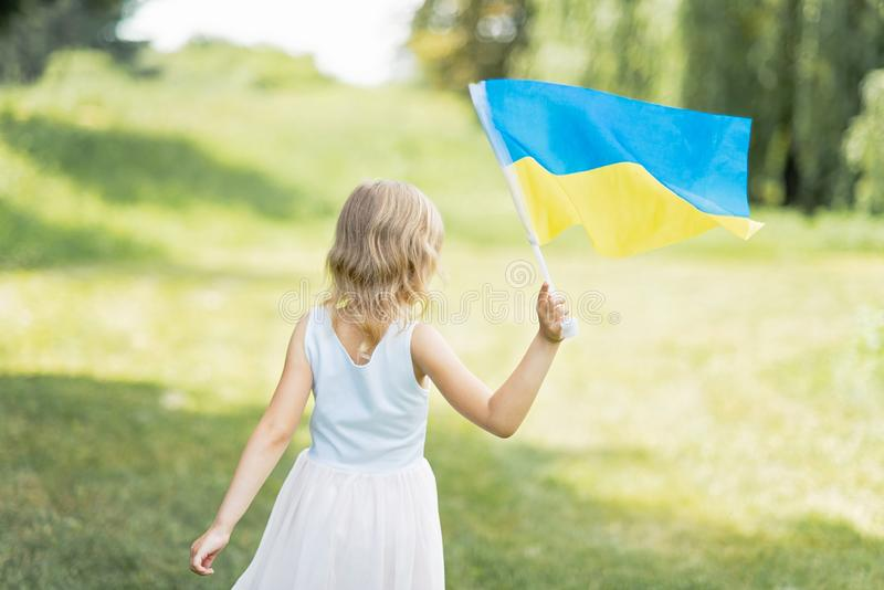 Child carries fluttering blue and yellow flag of Ukraine in field. Ukraine`s Independence Day. Flag Day. Constitution day. Girl i stock photos