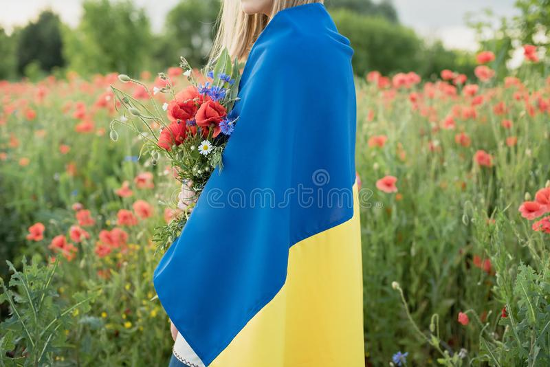 Child carries fluttering blue and yellow flag of Ukraine in poppy field. Ukraine's Independence Day. Flag Day. Background, beautiful, beauty, caucasian royalty free stock photo