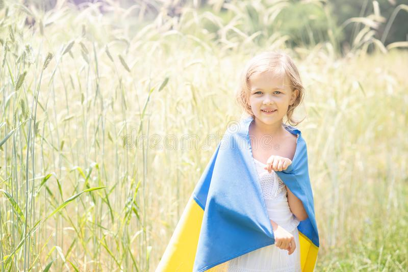 Child carries fluttering blue and yellow flag of Ukraine in wheat field. Ukraine& x27;s Independence Day. Flag Day. Background, banner, celebration, childhood royalty free stock images