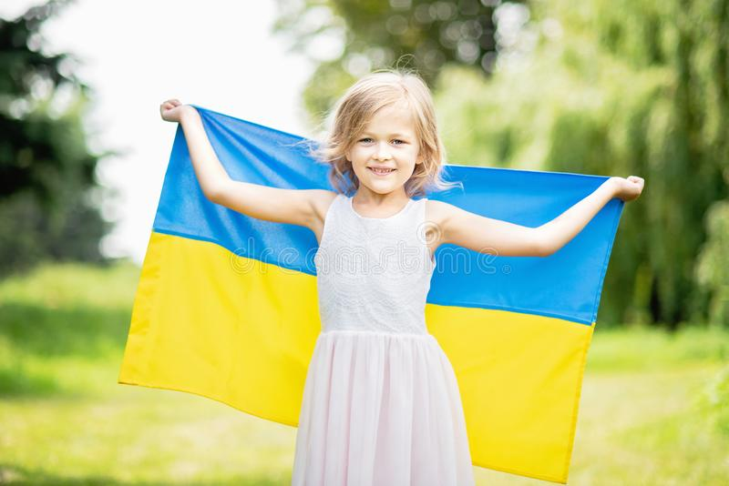 Child carries fluttering blue and yellow flag of Ukraine in wheat field. Ukraine& x27;s Independence Day. Flag Day. Background, banner, celebration, childhood stock photo