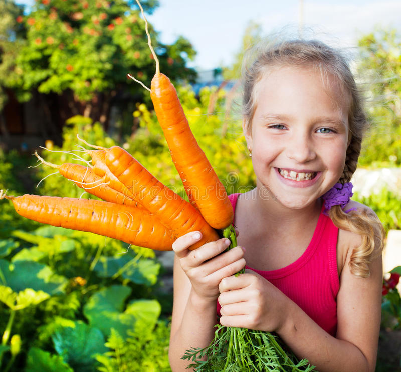 Child with carrot royalty free stock photography