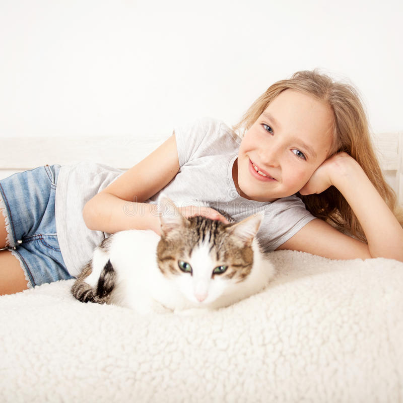 Child with cat. Girl with pet at home stock image