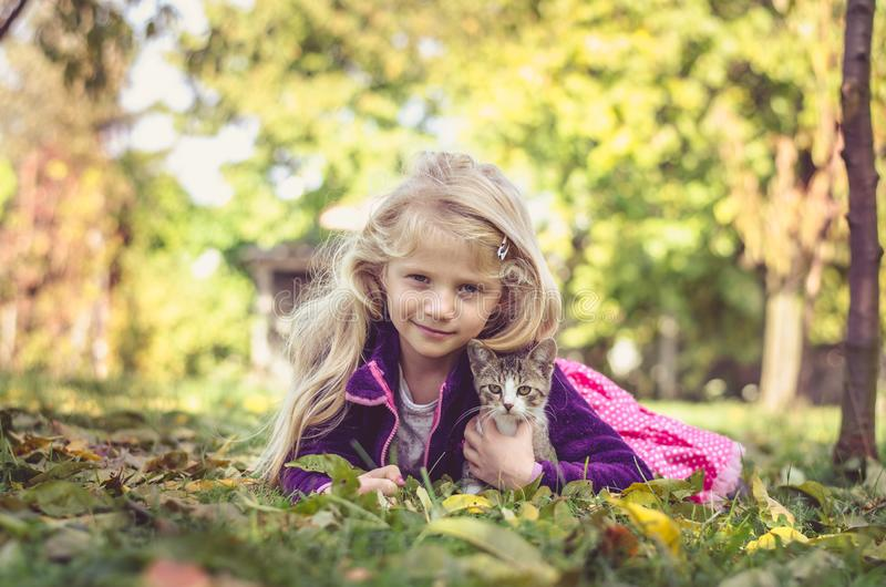 Child and cat relaxing on grass. Lovely blond girl with cat and lying together on grass in autumn time royalty free stock photos