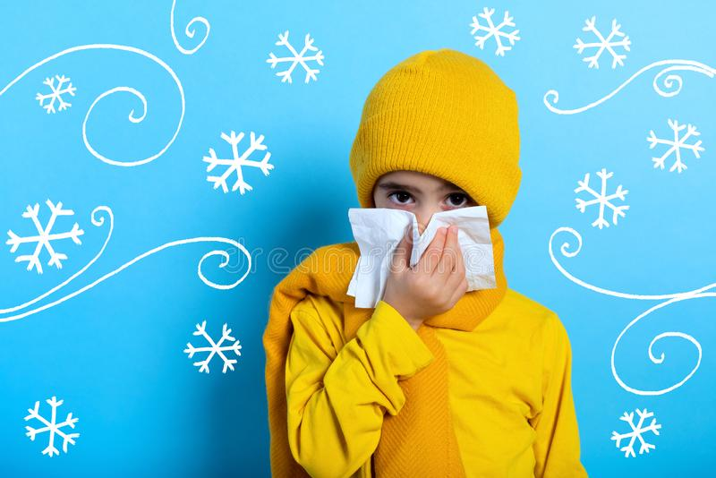 Child caught a cold and wipes her nose. Cyan background stock photo