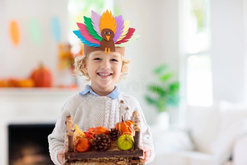 Child on Thanksgiving. Kid with autumn turkey hat. Child celebrating Thanksgiving. Kid holding pumpkin in paper turkey hat. Autumn fun crafts and art. Little stock image