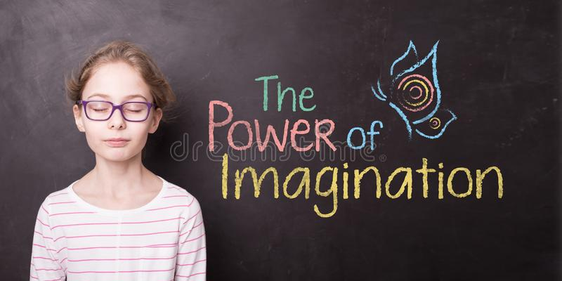 Child at the chalkboard and `The Power of Imagination` sign royalty free stock image