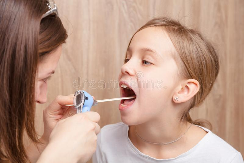 Child check up - doctor examining elementary age girl throat using wooden tongue depressor and torch royalty free stock photos