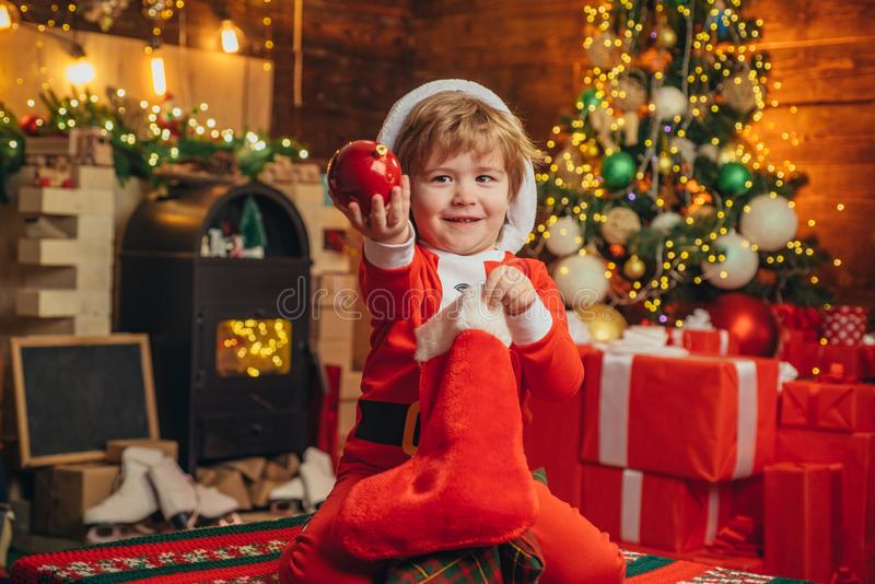Child cheerful face got gift in christmas sock. Check contents of christmas stocking. Joy and happiness. Childhood. Moments. Kid boy santa hold christmas gift stock images