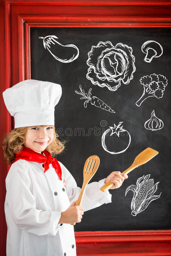 Child chef cook. Restaurant business concept. Child chef cook against blackboard blank menu with drawing healthy food. Restaurant business concept royalty free stock photography