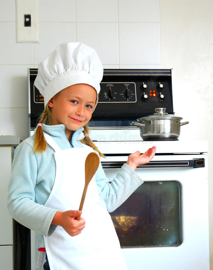 Child chef cooking. A cute little Caucasian girl child with white chef's hat, apron, wooden spoon and happy smiling expression in her pretty face presenting the royalty free stock photo