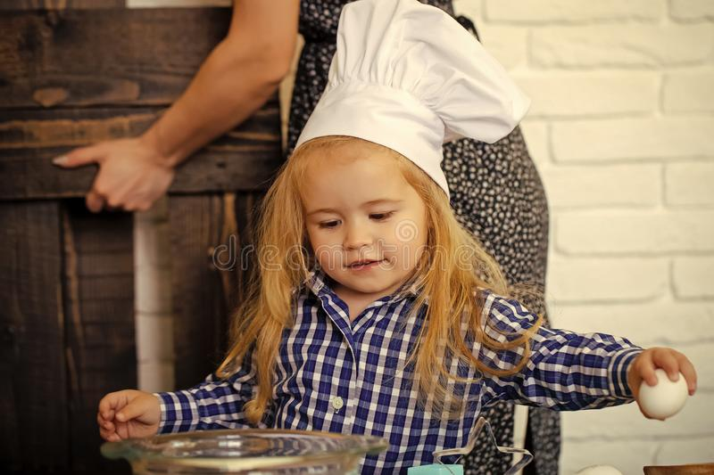 Child in chef hat breaking egg of bowl in kitchen royalty free stock photos