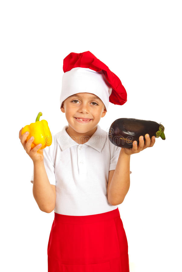 Child chef hold eggplant and pepper. Happy chef child holding eggplant and yellow bell pepper isolated on white background stock images