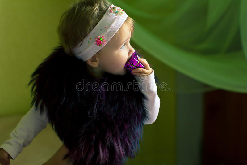 Child chews gift and looks into the distance. Child with fur on shoulders chews gift and looks into the distance stock photography