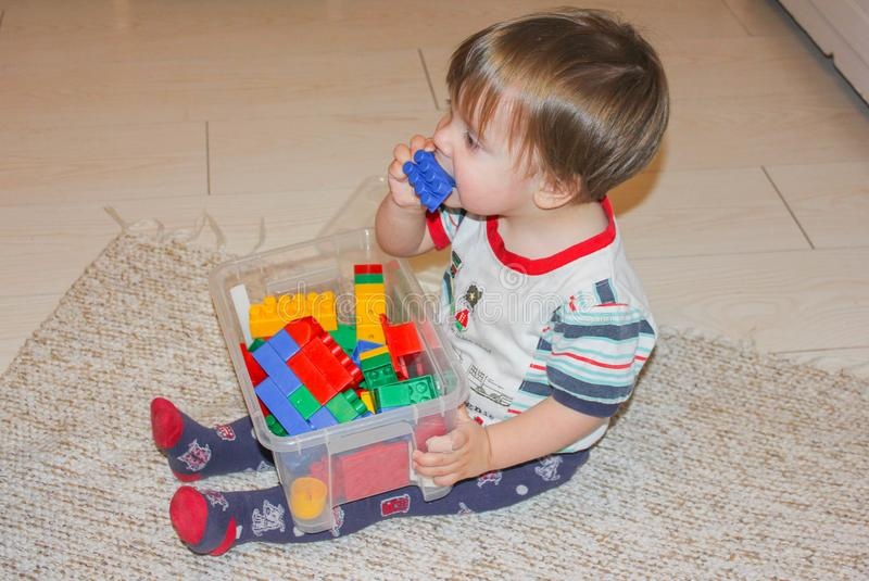 The child chews the toy. Little boy sitting on the floor and takes toy in her mouth. stock images