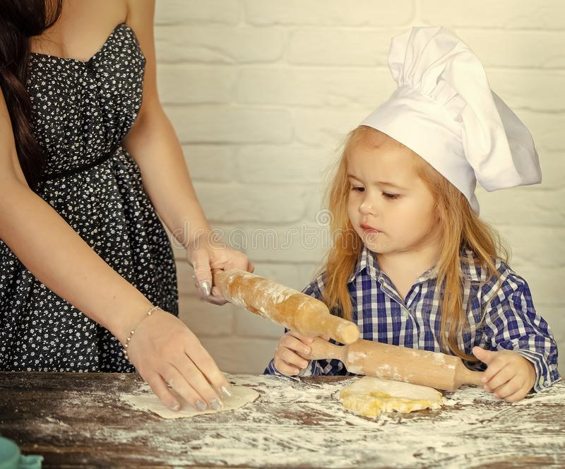 Child Childhood Children Happiness Concept. Child with serious face learning to roll dough royalty free stock photos