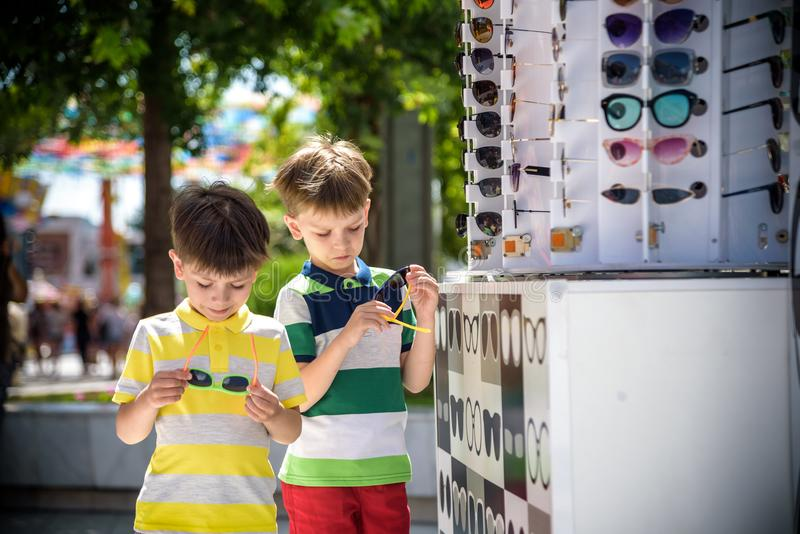 A child and a choice of sunglasses. Two little boys are standing in sun-proof glasses against the background of a shop window with stock images