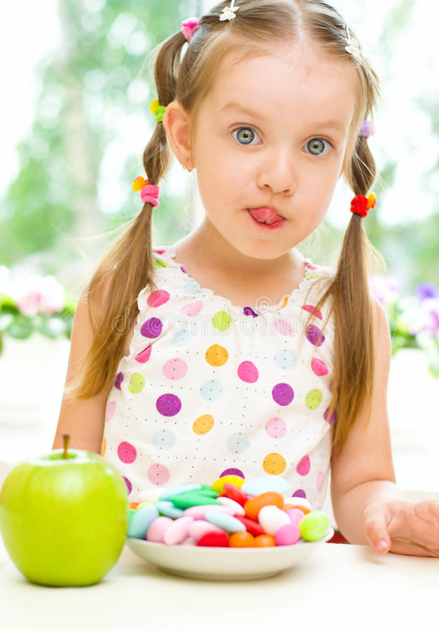 Child choosing between apple and sweets stock photography