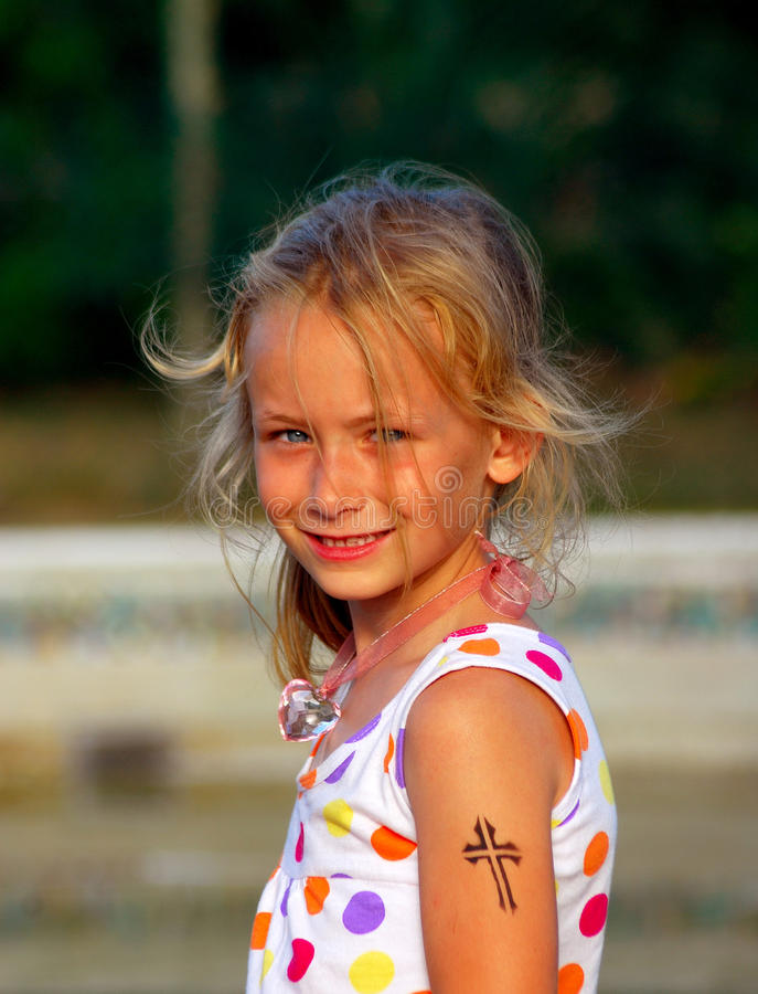 Child Christianity. Outdoor portrait of a cute little Caucasian girl child with happy smiling facial expression and Christian symbol tattoo (Jesus cross) on the stock images