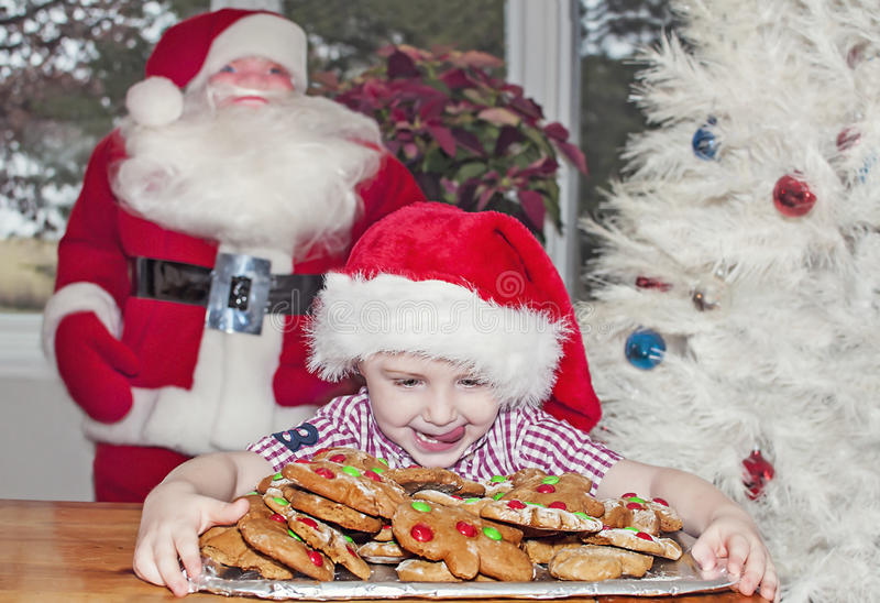 Child with Christmas cookies. Little boy wears a santa hat and looks eagerly at a plateful of Gingerbread man cookies. Santa and Christmas tree in the background stock photography