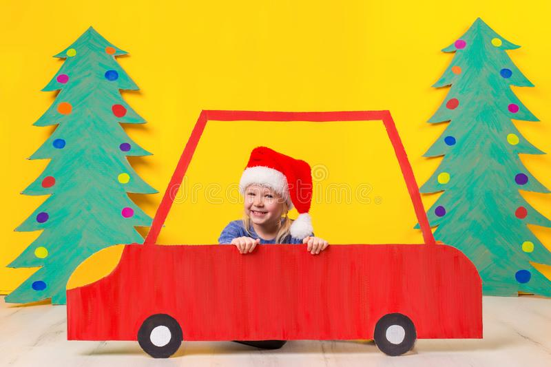 Child with Christmas hat driving a car made of cardboard. Christmas concept. New Year`s holidays. stock images