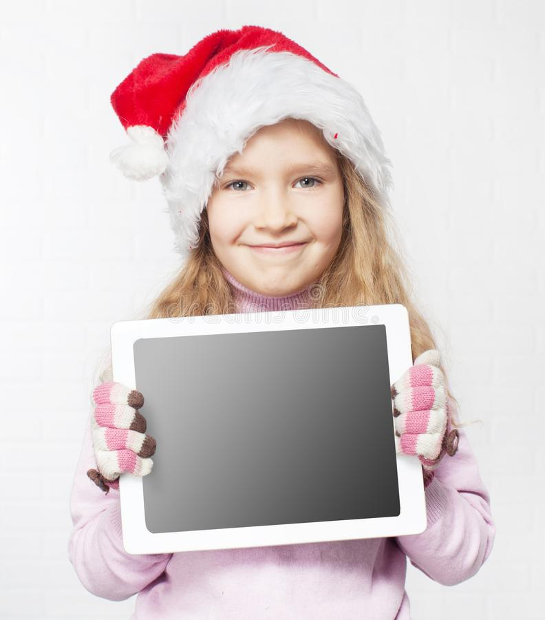 Child in christmas hat with tablet stock image