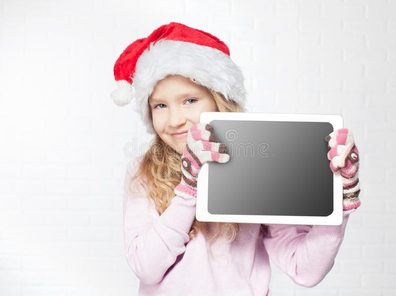 Child in christmas hat with tablet royalty free stock photo