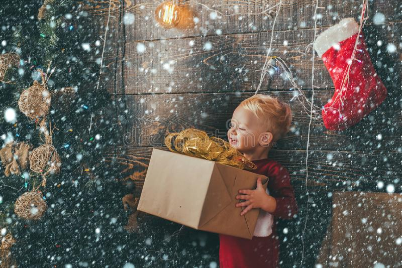 Child with a Christmas present on wooden background. Christmas card. Cute little kids celebrating Christmas. Happy child stock photo