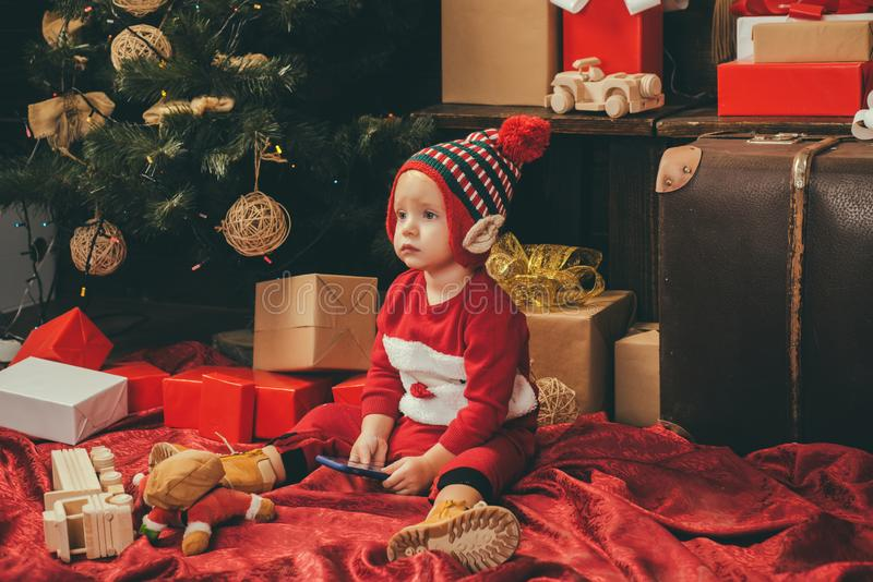 Child with a Christmas present on wooden background. Happy children. Babies. Winter kids. Christmas card. Christmas royalty free stock image