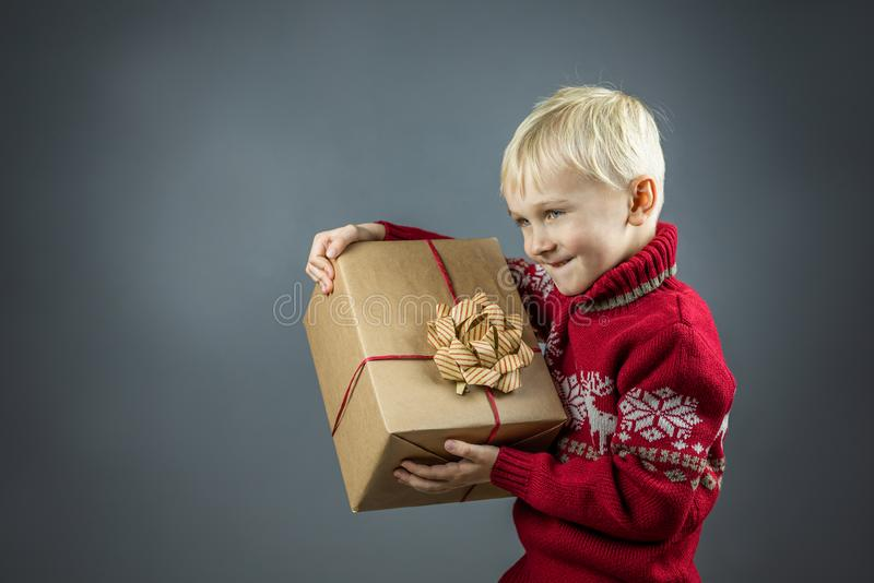 A child in a Christmas sweater holds a craft gift. Cute cheerful child in a Christmas sweater holds a big gift wrapped in kraft paper. The boy enjoys a lot of stock images
