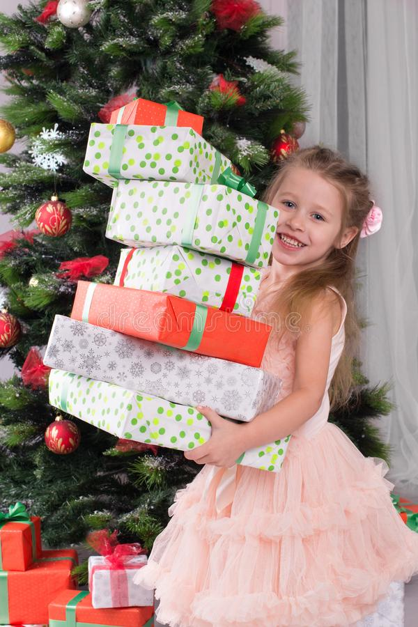 The child at Christmas tree holds boxes with gifts in hand. The girl at Christmas tree holds boxes with gifts in hand stock images
