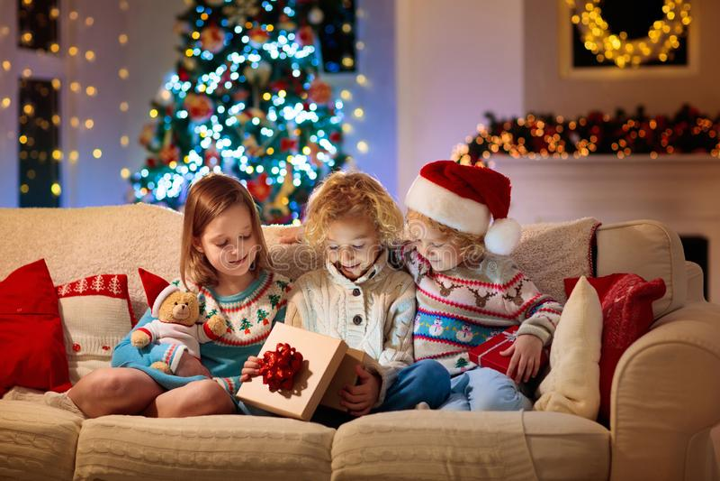 Child at Christmas tree. Kids at fireplace on Xmas stock photo