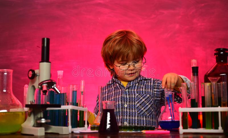 Child in the class room with blackboard on background. schoolboy. They carried out a new experiment in chemistry. Knowledge day. Home schooling. School concept stock image